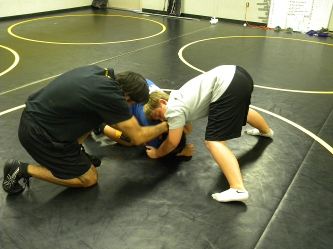 Coach Mestakides helps out with a front head lock.